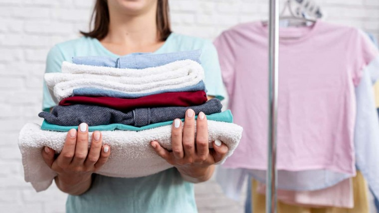 wash and fold close-up-woman-holding-folded-clothes-towels